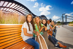 Happy friends sitting on wooden bench in a row Stock Photography