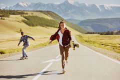 Happy friends with skates and longboards are having fun stock image