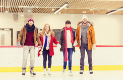 Happy friends on skating rink Stock Photos