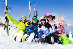 Happy friends after skiing sit on snow wave hands. Happy friends after skiing sitting on snow hug and wave hands with ski standing behind Royalty Free Stock Image