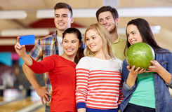 Happy friends with smartphone in bowling club Royalty Free Stock Images