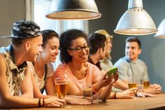 Happy friends with smartphone and drinks at bar Royalty Free Stock Photography