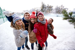 Happy friends with smartphone on ice skating rink Stock Photos