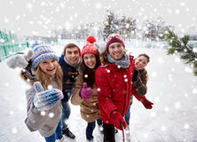 Happy friends with smartphone on ice skating rink Stock Image