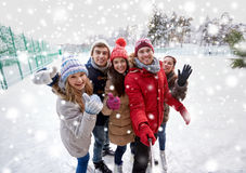 Happy friends with smartphone on ice skating rink Royalty Free Stock Image