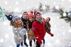 Happy friends with smartphone on ice skating rink Royalty Free Stock Photography