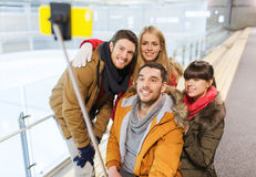 Happy friends with smartphone on skating rink Stock Image