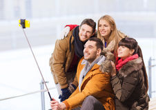 Happy friends with smartphone on skating rink Stock Photos
