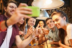 Happy friends with smartphone taking selfie at bar Stock Photography