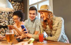 Happy friends with smartphones and drinks at bar Stock Images