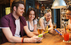 Happy friends with smartphones and drinks at bar Royalty Free Stock Photos