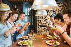 Happy friends with smartphones picturing food. People, leisure, friendship, technology and internet addiction concept - group of happy smiling friends with Stock Photography