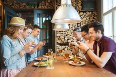 Happy friends with smartphones picturing food. People, leisure, friendship, technology and internet addiction concept - group of happy smiling friends with Stock Photos