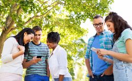 Happy friends with smartphones at summer park royalty free stock images