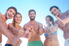 Happy friends smiling at camera showing thumbs up Stock Photography