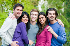 Happy friends smiling together outdoor. Young group of happy friends embracing and staying together outdoor in the park Royalty Free Stock Photography