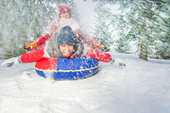 Happy friends on snow tube in winter during day Stock Images