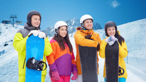 Happy friends with snowboards over mountains Royalty Free Stock Images