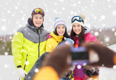 Happy friends with snowboards and smartphone Stock Photos
