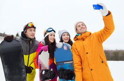 Happy friends with snowboards and smartphone Royalty Free Stock Image