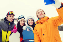 Happy friends with snowboards and smartphone Stock Photo