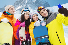 Happy friends with snowboards and smartphone Royalty Free Stock Photography