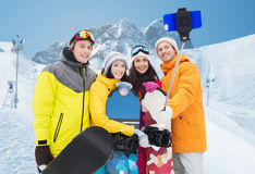 Happy friends with snowboards and smartphone Royalty Free Stock Images