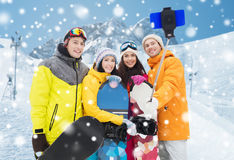 Happy friends with snowboards and smartphone Stock Photography