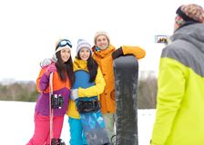 Happy friends with snowboards and smartphone Stock Images