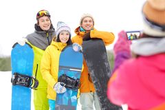 Happy friends with snowboards and smartphone Stock Image