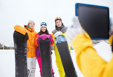 Happy friends with snowboards and tablet pc Stock Photography