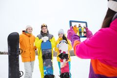 Happy friends with snowboards and tablet pc Royalty Free Stock Image