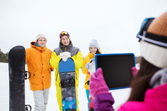 Happy friends with snowboards and tablet pc Royalty Free Stock Photography
