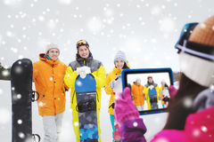 Happy friends with snowboards and tablet pc Stock Image