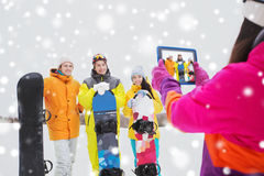 Happy friends with snowboards and tablet pc Royalty Free Stock Photo