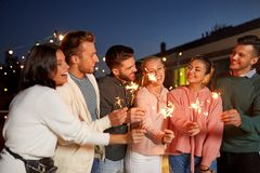 Happy friends with sparklers at rooftop party royalty free stock photos