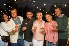 Happy friends with sparklers at rooftop party stock image
