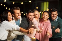 Happy friends with sparklers at rooftop party royalty free stock photography