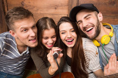 Happy friends spending their free time singing karaoke Stock Image