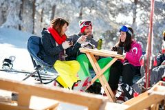 Happy friends spending time together and drink after skiing in c Royalty Free Stock Images