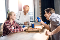 Happy friends spending time together with pizza and soda drinks Stock Images
