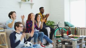Happy friends sport fans watching sports game on TV at home. They cheering up favorite team and clapping hands. Group of happy friends watching sports game on TV stock video footage