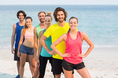 Happy friends in sports clothing standing at beach Stock Image