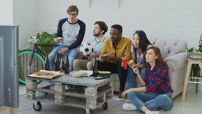 Happy friends sports fans watching football championship on TV together eating pizza and drinking beer at home. Indoors stock footage