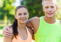 Happy friends or sportsmen couple hugging outdoors. Fitness, sport, friendship and healthy lifestyle concept - group of happy teenage friends or sportsmen couple Stock Photo