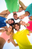 Happy friends standing with arm around against sky Royalty Free Stock Images