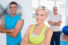 Happy friends standing arms crossed at gym class Royalty Free Stock Photography