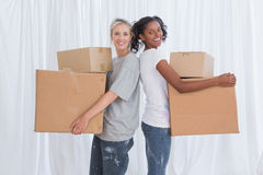 Happy friends standing back to back holding moving boxes Stock Photography