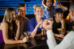 Happy friends standing at bar counter. Happy friends standing at counter in bar Stock Photo