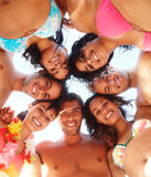 Happy friends standing a circle at the beach Stock Photography
